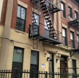 Front of brick building with fire escape